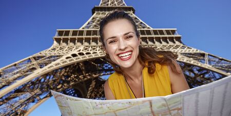 touristy: Touristy, without doubt, but yet so fun. Portrait of happy young woman with map against Eiffel tower in Paris, France