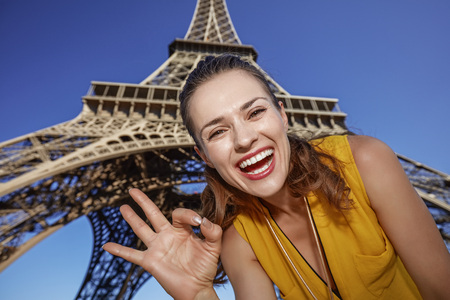 touristy: Touristy, without doubt, but yet so fun. Portrait of smiling young woman showing ok gesture in the front of Eiffel tower in Paris, France
