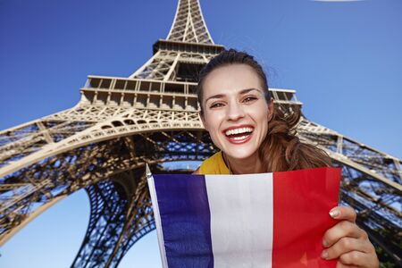 touristy: Touristy, without doubt, but yet so fun. Portrait of smiling young woman showing flag against Eiffel tower in Paris, France Stock Photo