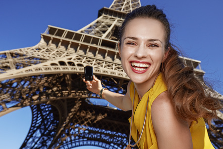 touristy: Touristy, without doubt, but yet so fun. Portrait of smiling young woman taking photo with digital camera against Eiffel tower in Paris, France