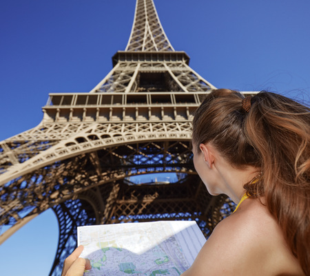 touristy: Touristy, without doubt, but yet so fun. Seen from behind young woman with map against Eiffel tower in Paris, France Stock Photo