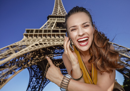 touristy: Touristy, without doubt, but yet so fun. Portrait of happy young woman speaking on a cell phone and pointing in the front of Eiffel tower in Paris, France Stock Photo