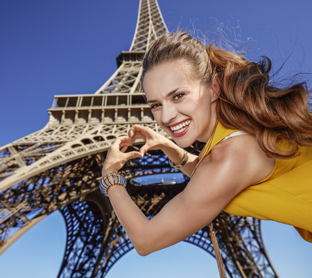 shaped hands: Touristy, without doubt, but yet so fun. smiling young woman showing heart shaped hands against Eiffel tower in Paris, France Stock Photo