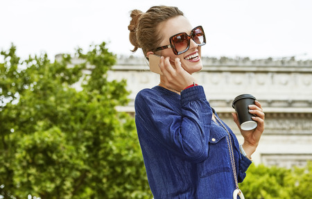 champ: Get your bags ready for the Paris shopping. smiling young elegant woman in sunglasses while drinking coffee on Champ Elysees Stock Photo
