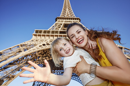 touristy: Touristy, without doubt, but yet so fun. Portrait of happy mother and daughter handwaving against Eiffel tower in Paris, France Stock Photo