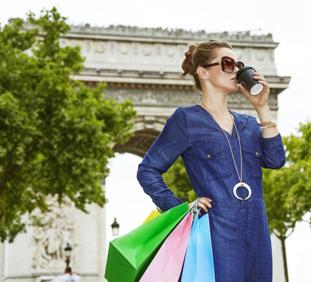 champ: Get your bags ready for the Paris shopping. young trendy woman in sunglasses drinking coffee on Champ Elysees