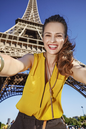 touristy: Touristy, without doubt, but yet so fun. happy young woman taking selfie against Eiffel tower in Paris, France Stock Photo