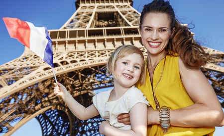 touristy: Touristy, without doubt, but yet so fun. smiling mother and daughter travellers showing flag against Eiffel tower in Paris, France Stock Photo