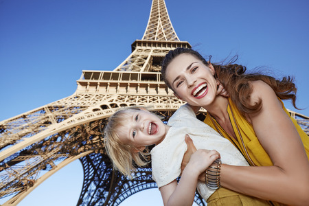 touristy: Touristy, without doubt, but yet so fun. Portrait of cheerful mother and daughter travellers against Eiffel tower in Paris, France Stock Photo