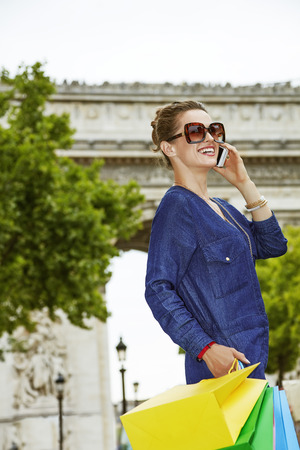 champ: Get your bags ready for the Paris shopping. happy young fashion-monger in sunglasses talking on a cell phone on Champ Elysees Stock Photo