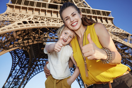 touristy: Touristy, without doubt, but yet so fun. Portrait of happy mother and daughter travellers showing thumbs up against Eiffel tower in Paris, France