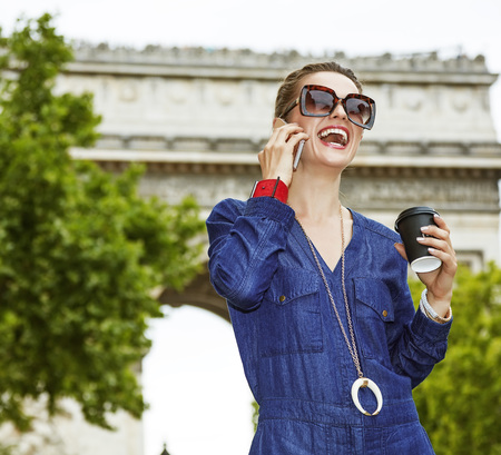 champs elysees: Get your bags ready for the Paris shopping. smiling young fashion-monger with shopping bags using a smartphone while drinking coffee on Champ Elysees