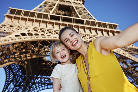 touristy: Touristy, without doubt, but yet so fun. Portrait of smiling mother and child taking selfie in the front of Eiffel tower in Paris, France Stock Photo