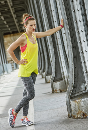 Outdoors fitness in Paris. young woman jogger relaxing after workout on Pont de Bir-Hakeim bridge in Paris