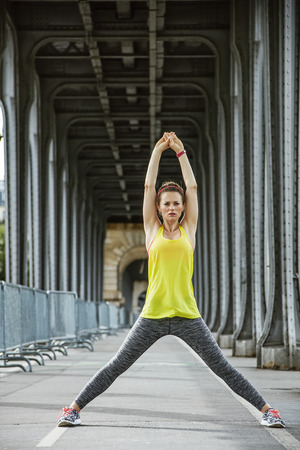 Outdoors fitness in Paris. Full length portrait of young sportswoman stretching on Pont de Bir-Hakeim bridge in Paris Stock Photo