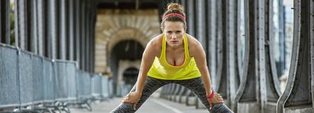 bir: Outdoors fitness in Paris. Full length portrait of young healthy woman stretching on Pont de Bir-Hakeim bridge in Paris