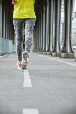 bir: Jogging in Paris. Closeup on young woman jogger running on Pont de Bir-Hakeim bridge in Paris