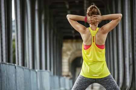 bir: Outdoors fitness in Paris. Seen from behind young sportswoman stretching on Pont de Bir-Hakeim bridge in Paris Stock Photo