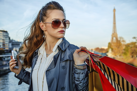 Get your bags ready for the Paris autumn sales. young elegant woman with shopping bags  in Paris, France looking aside while holding smartphone