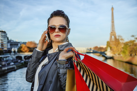 trench coat: Get your bags ready for the Paris autumn sales. Portrait of young trendy woman in trench coat with shopping bags using a smartphone in Paris, France