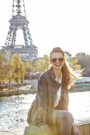 escapadas de otoño en París. Retrato de la mujer elegante joven sonriente en gafas de sol en el terraplén en París, Francia, sentado en el parapeto