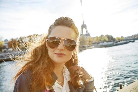 Autumn getaways in Paris. Portrait of young elegant woman in sunglasses on embankment in Paris, France