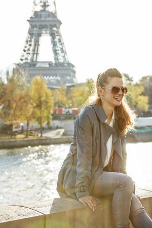 escapadas de otoño en París. sonriente mujer joven y elegante en gafas de sol en el terraplén en París, Francia, sentado en el parapeto