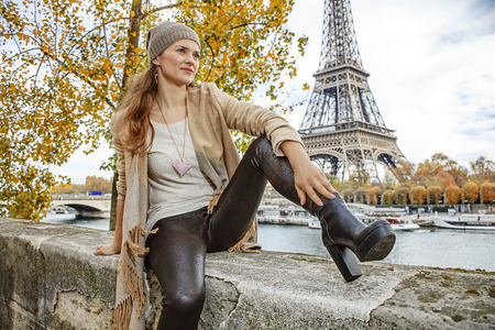 Autumn getaways in Paris. young elegant woman on embankment in Paris, France looking into the distance while sitting on parapet Stock Photo
