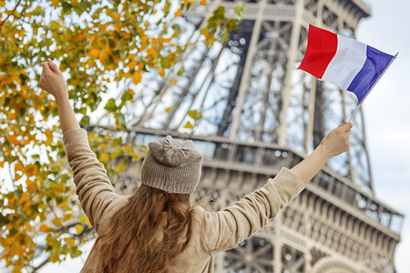 anonym: Autumn getaways in Paris. Seen from behind young elegant woman on embankment in Paris, France rising flag Stock Photo