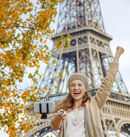 rejoicing: Autumn getaways in Paris. cheerful young tourist woman on embankment in Paris, France rejoicing and taking selfie using selfie stick Stock Photo