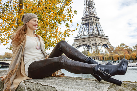 parapet: Autumn getaways in Paris. happy young elegant woman on embankment in Paris, France looking into the distance while sitting on parapet