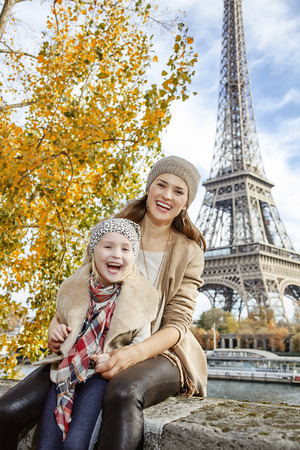 parapet: Autumn getaways in Paris with family. Portrait of smiling mother and child travellers on embankment near Eiffel tower in Paris, France sitting on the parapet