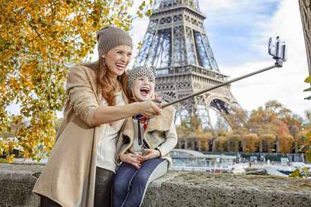 parapet: Autumn getaways in Paris with family. happy mother and daughter tourists on embankment near Eiffel tower in Paris, France taking selfie while sitting on the parapet