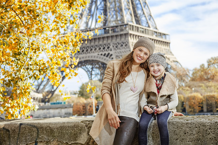 parapet: Autumn getaways in Paris with family. Portrait of happy mother and child tourists on embankment in Paris, France sitting on the parapet