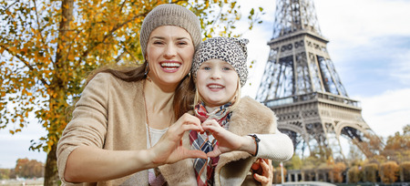shaped hands: Autumn getaways in Paris with family. Portrait of happy mother and daughter tourists on embankment near Eiffel tower in Paris, France showing heart shaped hands