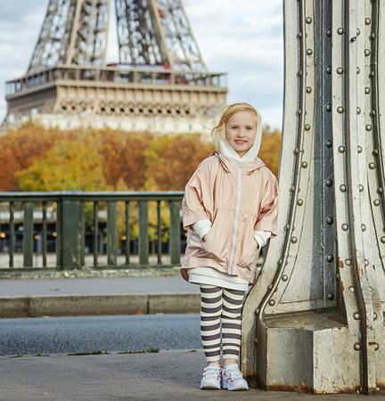 bir: Year round fit & hip in Paris. Full length portrait of happy active girl in sport style clothes standing on Pont de Bir-Hakeim bridge in Paris