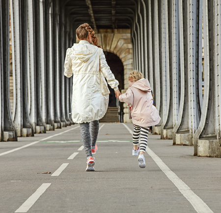 anonym: Year round fit & hip in Paris. Seen from behind smiling healthy mother and daughter in sport style clothes on Pont de Bir-Hakeim bridge in Paris walking