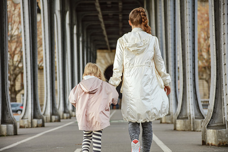 anonym: Year round fit & hip in Paris. Seen from behind healthy mother and child in sport style clothes on Pont de Bir-Hakeim bridge in Paris walking Stock Photo