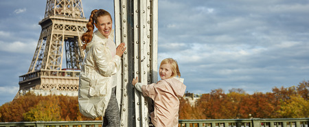 Year round fit & hip in Paris. Full length portrait of smiling healthy mother and daughter in sport style clothes on Pont de Bir-Hakeim bridge in Paris having fun time Stock Photo