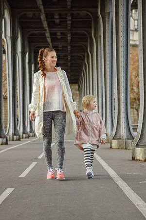 bir: Year round fit & hip in Paris. Full length portrait of happy active mother and child in sport style clothes on Pont de Bir-Hakeim bridge in Paris walking