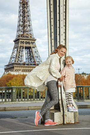 Year round fit & hip in Paris. Full length portrait of happy active mother and child in sport style clothes standing on Pont de Bir-Hakeim bridge in Paris Stock Photo