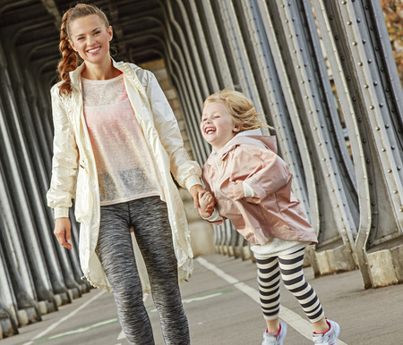 Year round fit & hip in Paris. cheerful healthy mother and child in sport style clothes on Pont de Bir-Hakeim bridge in Paris walking Stock Photo