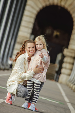 Year round fit & hip in Paris. Full length portrait of smiling healthy mother and daughter in sport style clothes on Pont de Bir-Hakeim bridge in Paris pointing in camera