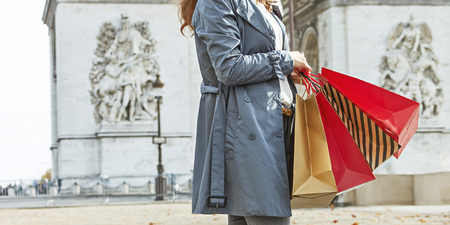 Stylish autumn in Paris. Closeup on happy trendy woman in trench coat with shopping bags in Paris, France Stock Photo