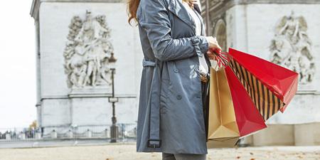 otoño con estilo en París. Primer en la mujer de moda feliz en gabardina con bolsas de compras en París, Francia