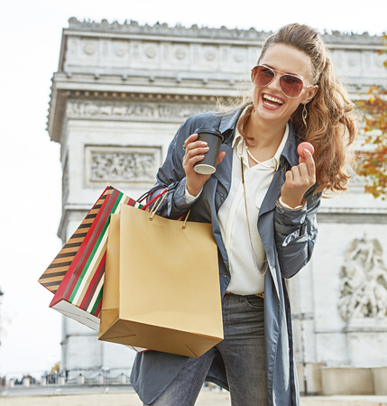 Stylish autumn in Paris. Portrait of smiling young woman in sunglasses with shopping bags near Arc de Triomphe in Paris, France having coffee and macaroon Stock Photo