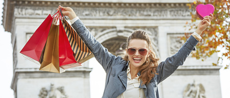 champs elysees: Stylish Valentines Day in Paris. smiling elegant fashion-monger in sunglasses with shopping bags in Paris, France showing red heart shaped box of chocolates and rejoicing