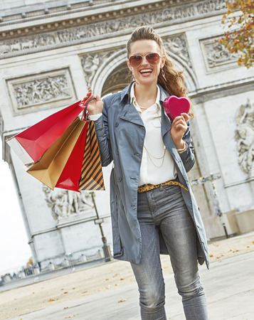 Stylish Valentines Day in Paris. smiling trendy fashion-monger in sunglasses with shopping bags in Paris, France showing red heart shaped box of chocolates Stock Photo