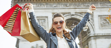 rejoicing: Stylish autumn in Paris. smiling elegant woman in sunglasses with shopping bags in Paris, France rejoicing