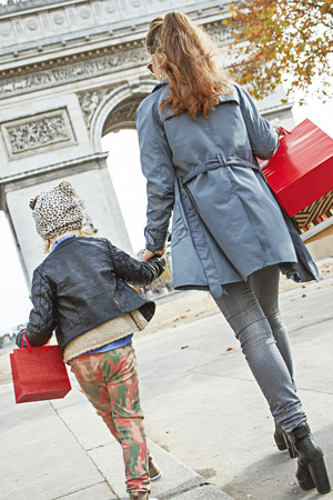 Stylish autumn in Paris. Seen from behind young mother and child with shopping bags in Paris, France walking